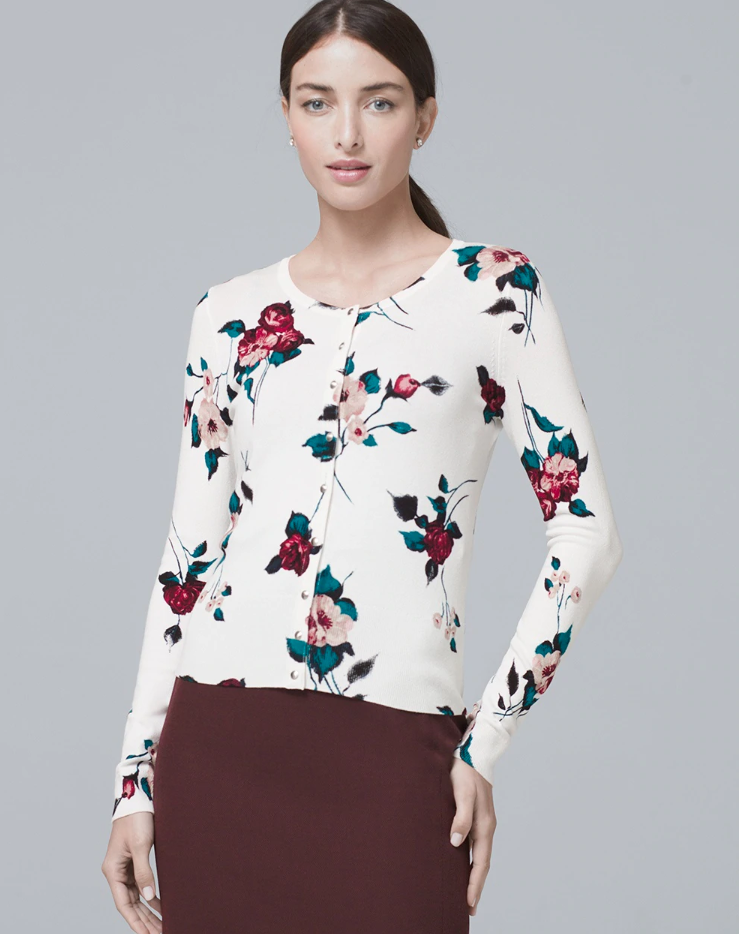 A woman in a floral snap-front cardigan stands against a gray background