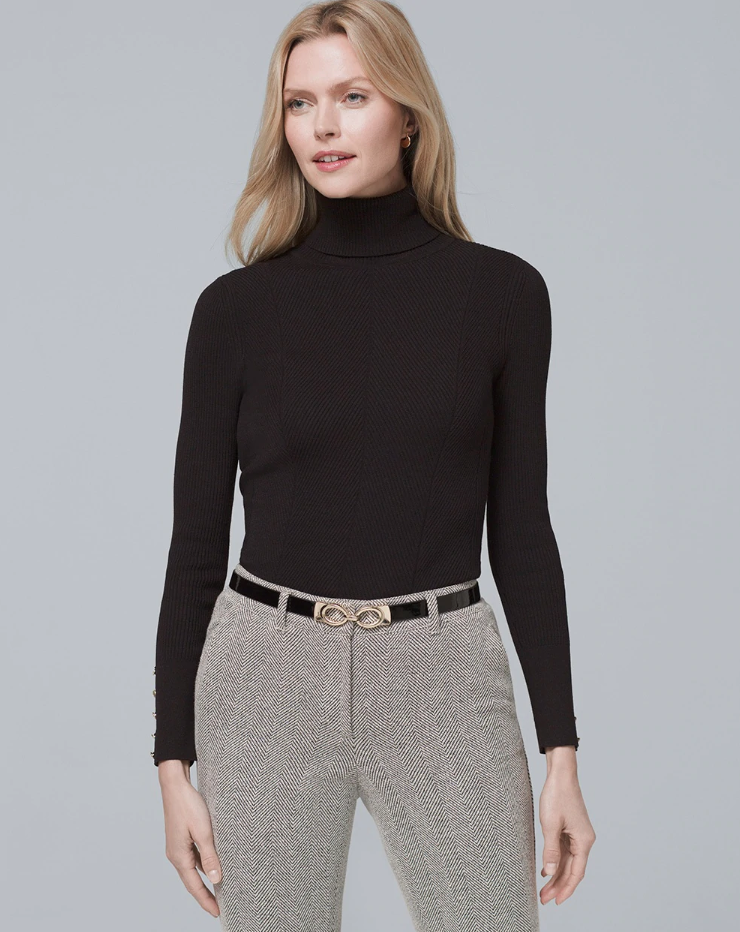 A blonde woman in a black turtleneck and herringbone tweed trousers stands against a gray background