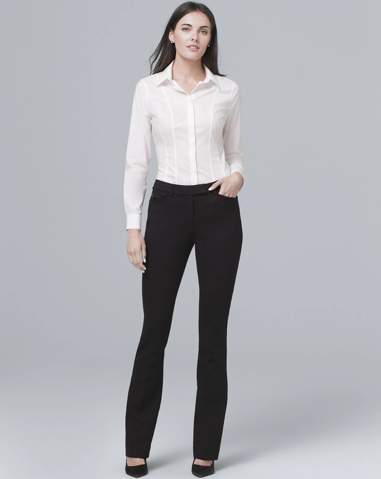 A brunette woman in black pants and a white shirt poses against a gray background