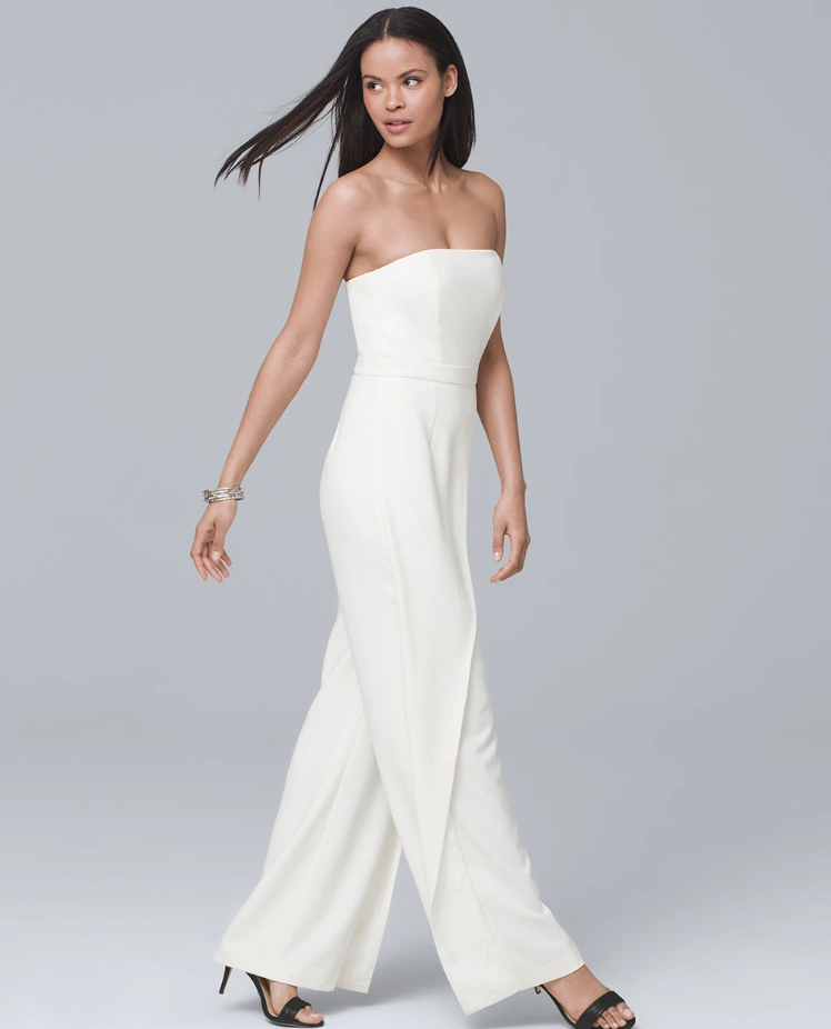 A brunette woman walks across a gray background wearing a strapless white jumpsuit with wrap trim.