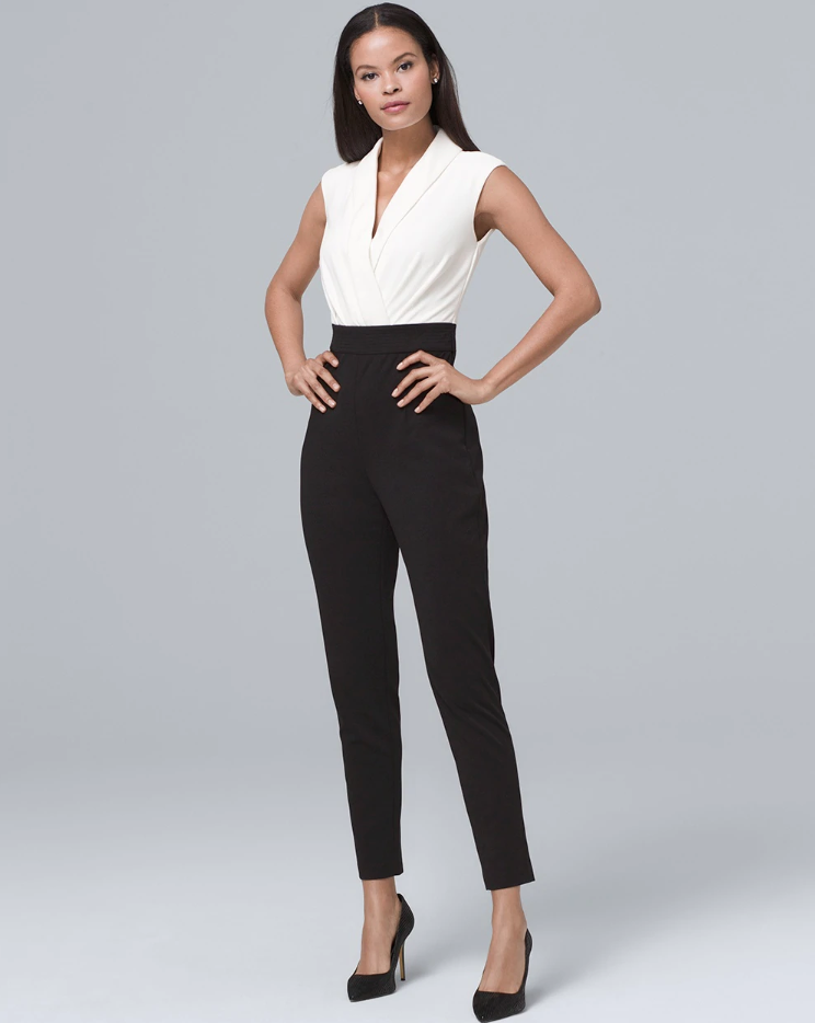 A brunette woman stands on a gray background, wearing a jumpsuit with a white blouse top