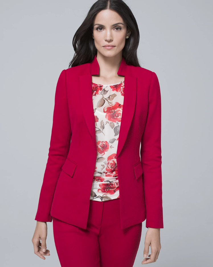 A brunette woman in a gray room wears a red suit with a floral shell
