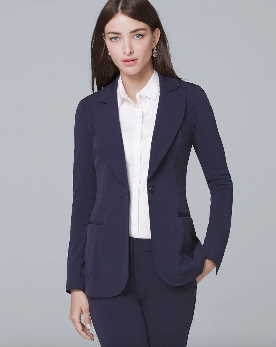 Brunette woman in a long, hip-length navy blue blazer with one button